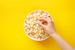 hand going into a tub of popcorn with yellow background