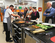 Cookery class with people standing around watching chef cook in a pan on stove