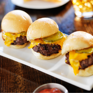 three mini burger sliders on a rectangular plate