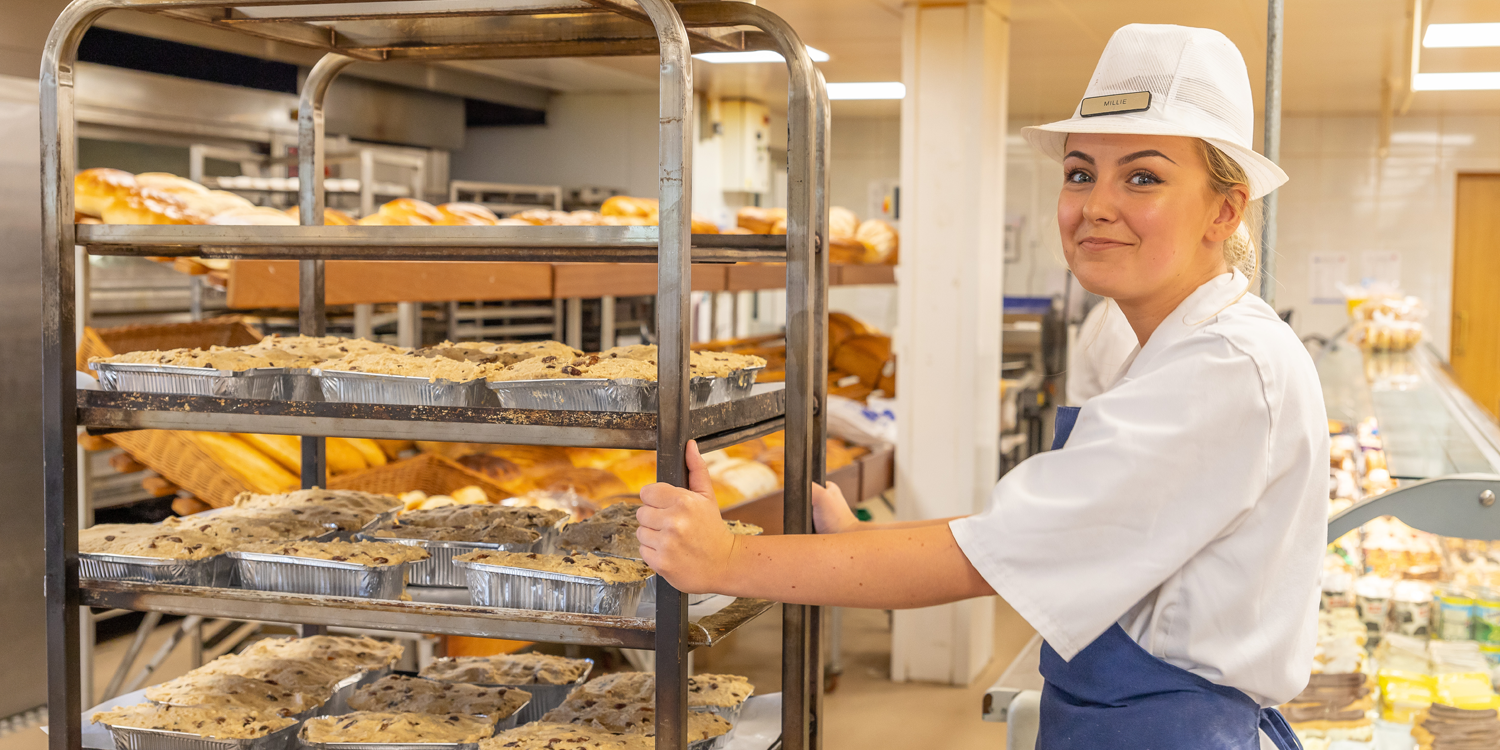 bakery staff member pushes trolly of bread and butter pudding