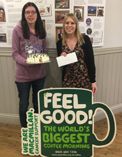 bake off competition winner gemma stands with cake and macmillan poster